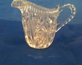 A clear glass creamer with deep wedges throughout with handle. Dish 561
