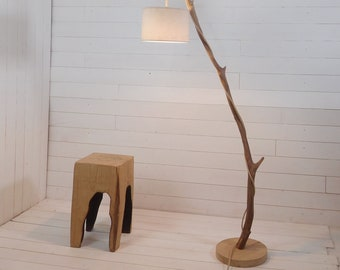 Natural wood standing lamp with exposed cable and hanging light
