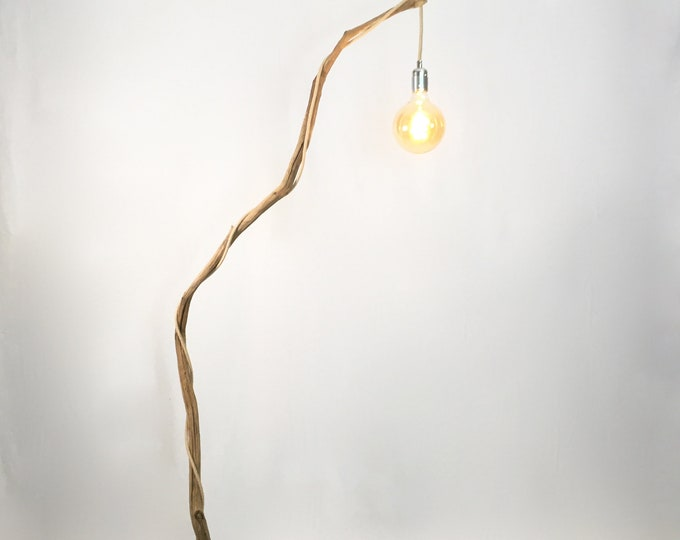 Weathered twisted branch standing lamp with hanging vintage bulb