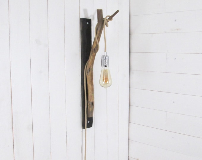 Wall lighting with a branch on a black painted board