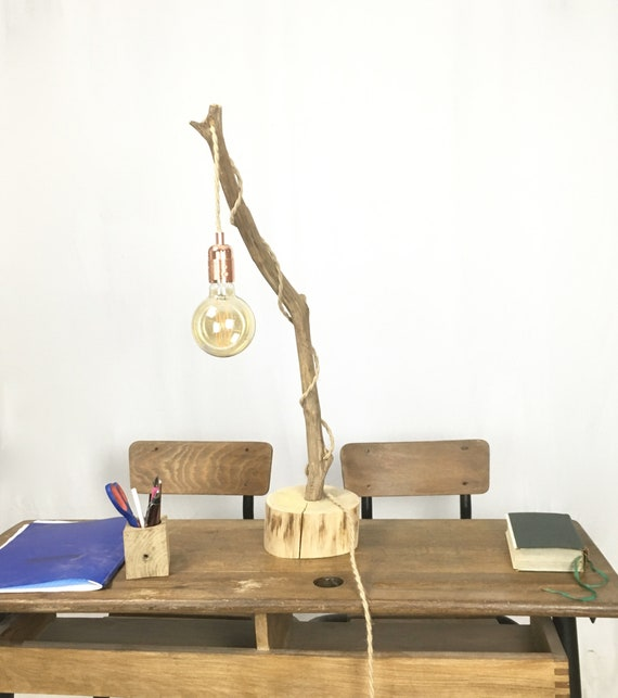 Rustic branch lamp with a hanging bulb and twisted jute flex