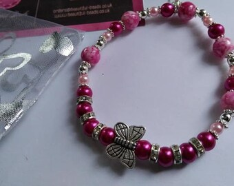 Pink beaded stretch bracelet with butterfly and charm