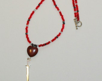 Swordheart Necklace: jasper heart and silvery sword charm on a string of red, black, and white seed beads
