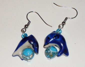 Day of the Dolphin: earrings with navy blue ceramic dolphins leaping over blue marble