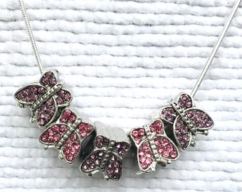 """A rhinestone butterfly necklace with 5 rhinestone butterflies . """" Pink Butterfly Necklace """"."""