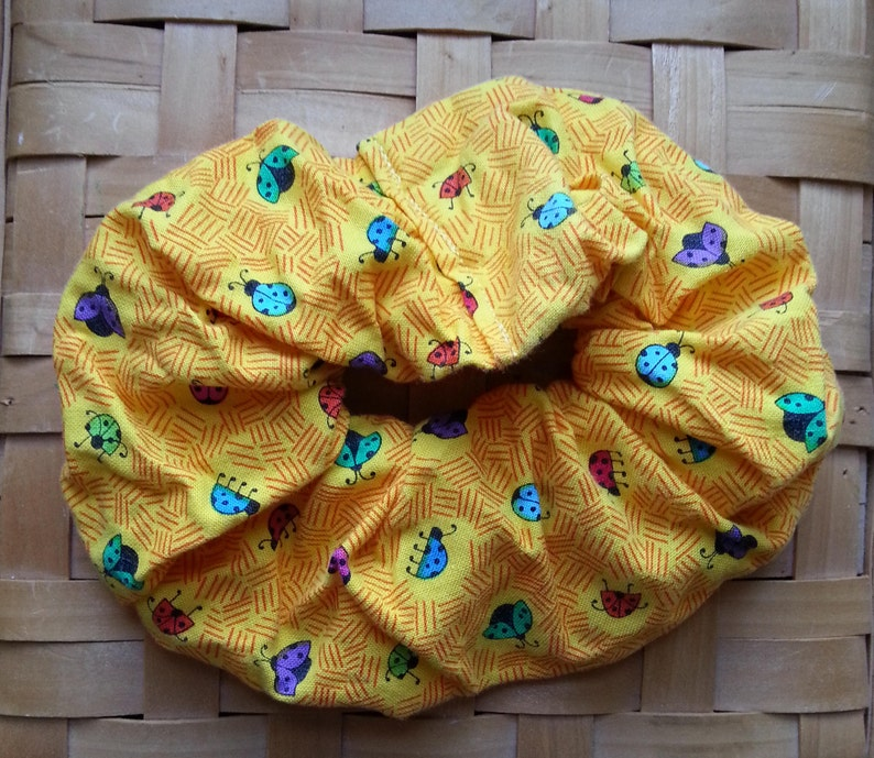 Yellow hair scrunchie with multi-colored lady bugs