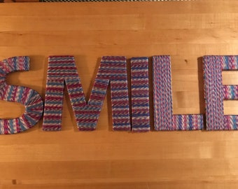 """8"""" five letter word """"SMILE"""" wrapped in purple/blue/red/yellow yarn"""