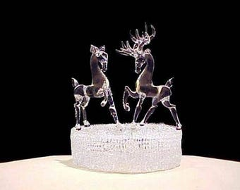 Deer wedding cake topper with a buck and a doe on a knitted glass base..