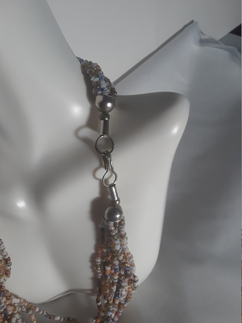 A multistranded seed beaded necklace with soft colors.