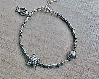 Ocean theme Karen Hill Tribe silver bracelet with daisy imprint tube beads and  seed beads, a starfish and fish bead and spiral fish charm