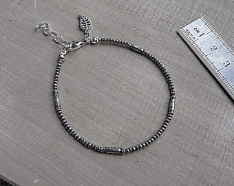 Karen Hill Tribe mix of tiny imprint seed beads and daisy imprint tube beaded bracelet with sterling silver leaf charm