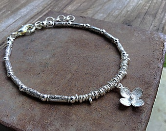 Karen Hill Tribe mix of irregular and daisy imprint tube beaded bracelet with sterling flower charm and tiny sterling spacers