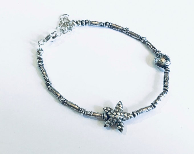Ocean theme Karen Hill Tribe silver bracelet with daisy imprint tube beads and  seed beads, a starfish and fish bead