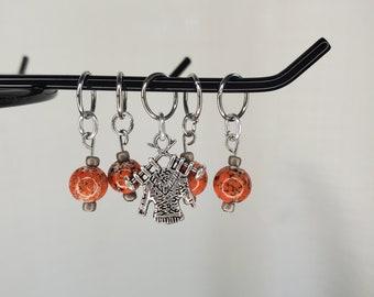 Orange with silver flecks glass bead stitch markers with sweater charm