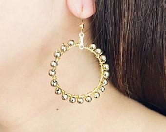 Gold bead wire wrapped hoop earrings.