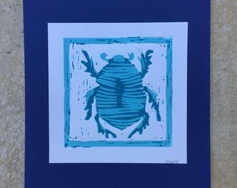 A Linocut of a Beetle printed in blue.