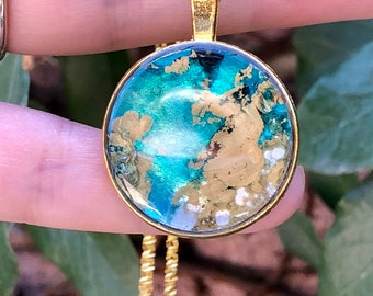 Glossy aqua and gold round watercolor pendant hung on 18 inch gold plated chain