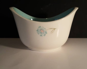 Vintage serving dish with teal accents.