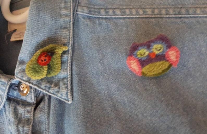 11 Vintage Handmade Felting and Rug Hooked Pins on Denim Shirt.