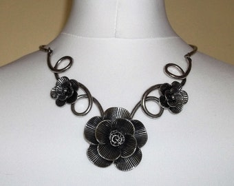 Stunning floral statement necklace in silver tones. Metal swirl neck fitting.