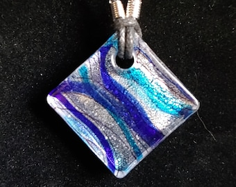 Clear, Glass, Diamond Pendant with Blue and Ribbon Stripes Embedded Within, With A Silver Background, Strung On Black, Faux Leather Cord.