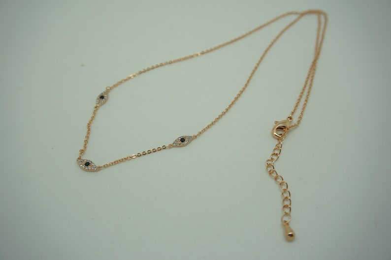 Stainless Steel rose gold necklace with three diamond black eyed charms