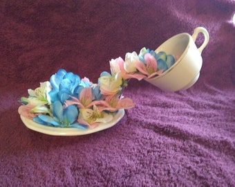 Teacup pouring flowers
