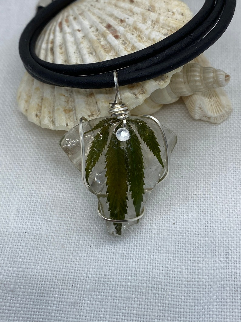 Handmade cannabis necklaces preserved on sea glass and coated in resin