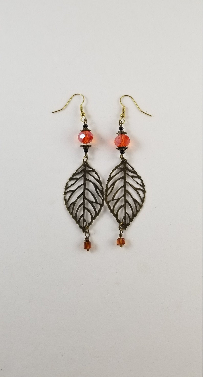 Bronze metal leaf coral glass bead dangle earrings with a Swarovksi crystal dangle on gold French hook wires for pierced ears.