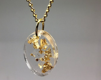 Gold Flakes set in a clear resin pendant hung on a gold plated chain