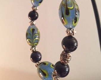 Stretch bracelet of Lampwork glass beads with goldstone and silver accents