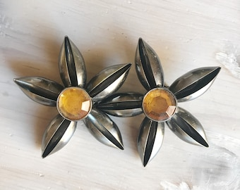 1980. Clip Earrings. Maxi earrings in the shape of a flower. Central ochre-coloured cabochon.