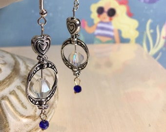 Romantic silver earrings with silver heart beads, clear crystal beads and a tinyblue dangle bead.