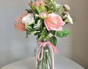 Medium sized hand tied arrangement of faux peach pink flowers in a clear glass vase