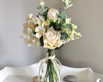 Small hand tied arrangement of faux ivory flowers in a clear glass vase
