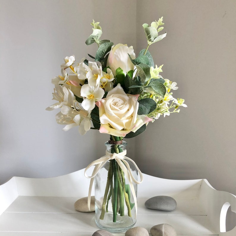 Small hand tied arrangement of faux ivory flowers in a clear image 0