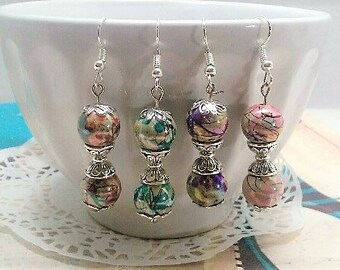Wonderful silver dangle earrings that come in choice of pink, red, purple and teal swirl beads.  Earrings have silver trimmings as well.