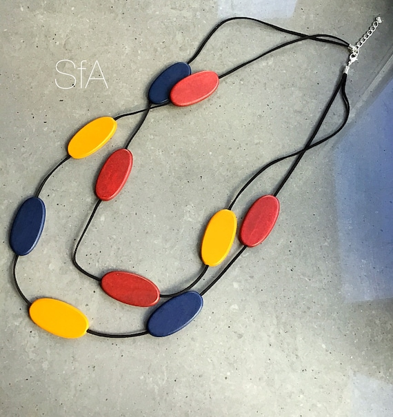 Long necklace made from wood, with multi coloured oval discs, with double black suede thread.