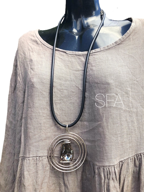 Lagenlook necklace. Large twisted rectangle wire pendant with central large crystal stone, on thick rubber necklace