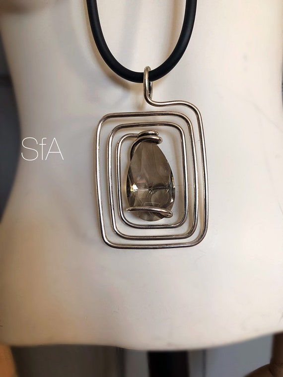 Lagenlook necklace. Large twisted rectangle wire pendant with central large teardrop glass crystal, on thick rubber necklace.