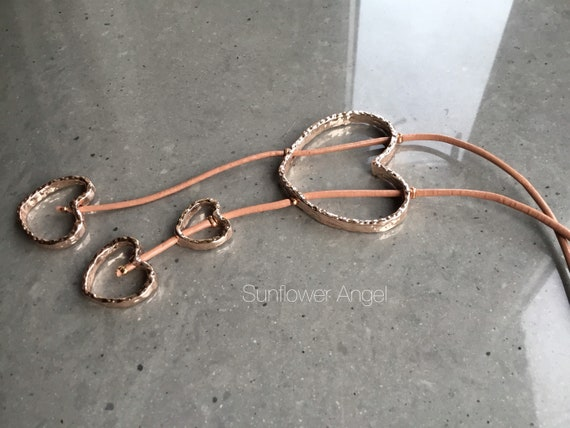 Gold multi heart necklace, on a caramel leather thread with various shaped gold hearts.