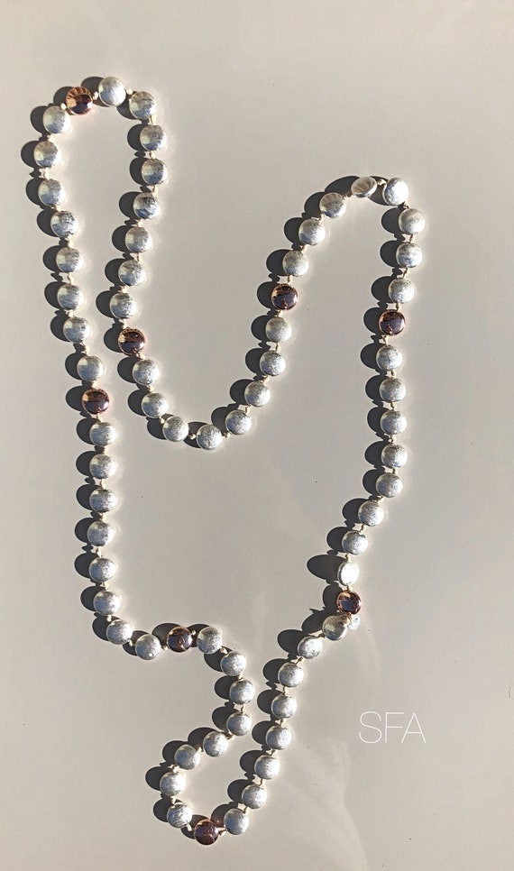 Long beaded tarnished necklace, with rose gold and tarnished silver beads on white thread.