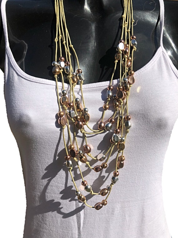Multi strand beaded necklce on twine, with lobster clasp with extension chain