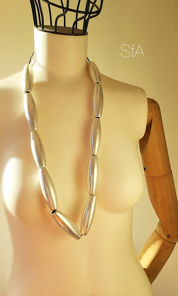 Metal solid Cone shaped beaded necklace, on a thin leather thread.