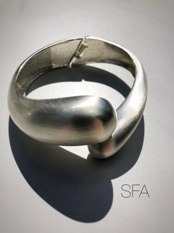 Abstract geo, bangle cuff, in brushed effect, silver with hinged opening.