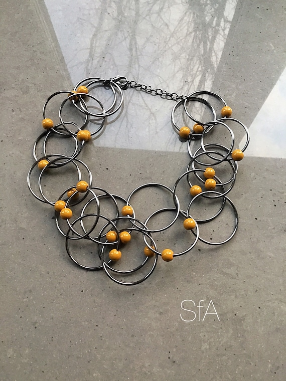 Geo metric necklace, lagenlook necklace, in gunmetal tone. With interlinked rings, and mustard beads.