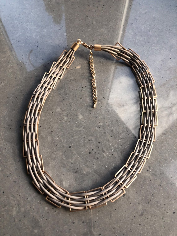 The Zoe multithread gold caged taupe necklace.