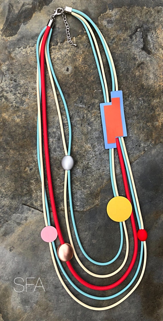 Lagenlook, Geo, multi thread rubber necklace, in red, cream and blue thread, with a dusky pink disc and gold frosted geo shapes.