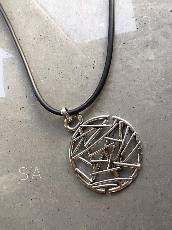 Lagenlook abstract necklace, with large round pendant, on a thick rubber thread.