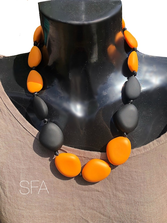 WoW cord necklace with mustard and black ceramic pepples, slight frosted, matt feel.